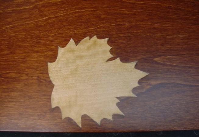 Kynttilän polttaman pöydän korjaus: Tein vaahteraviilusta vaahteranlehti-intarsian, koska asiakkaan nimi oli Vaahtera. Pöydön arvo kohosi merkittävästi.