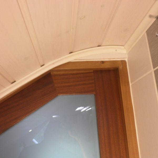 Kylpyhuone detalji. Haasteena katon lappeen mataluus. Räätälöity ovi ja kaareva katto kruunaavat tuloksen.
