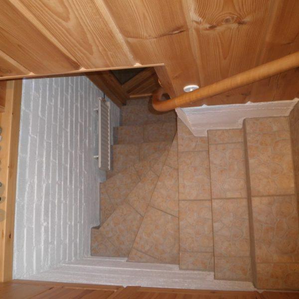 """Uudistin vanhan portaikon kokonaisuudessaan. Jyrkkyyttä pystyin korjaamaan vain hiukan valamalla joihinkin askelmiin vähän lisää leveyttä ja avartamalla alapään kulkuaukkoa.  Isot """"kivilaatat"""", järeä hirsipaneeli ja kalkkimaalattu tiili luovat jykevän vaikutelman, Kaareva kaidepuu loimukoivua."""