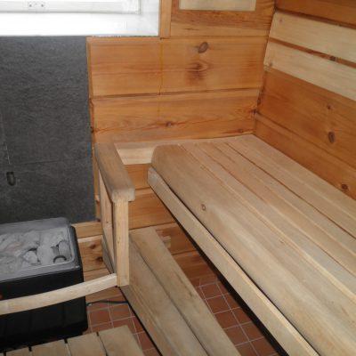 Saunanlaude haapaa, seinä järeää hirsipaneelia. Istuinosan kallistus on säädettävä. Laudetasot nostettavissa siivouksen helpottamiseksi.