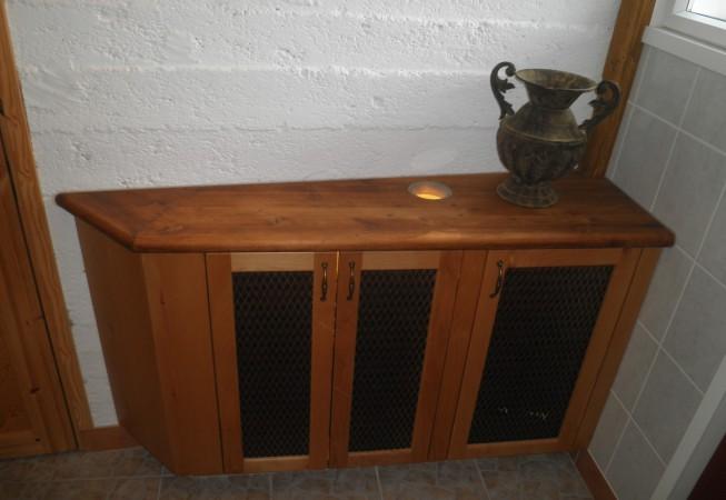 Englantilaistyylinen kaapisto pienessä saunan eteisessä. Kiilamainen muoto jättää hyvän kulkutien. Amerikkalaista leppää, taso värivahattua mäntyä, ovissa messinkiverkot. Tasossa oleva valaistu ikkuna on vesimittarin lukua varten.