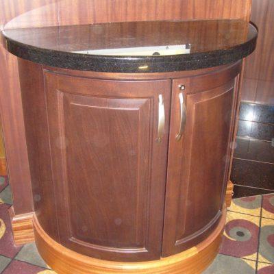 Pyöreä kaappi. Ravintola Chops Grille. Laivat: Oasis of the Seas 2009 ja Allure of the Seas 2010. Tumma mahonki ja musta kivi. Jalkalista vaalea mahonki.